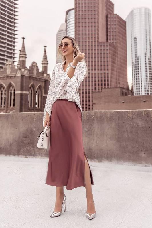 une tenue de travail avec une chemise rayée, une jupe-culotte mauve, des talons argentés et un sac blanc pour le printemps