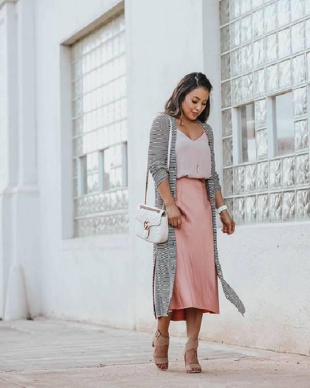 un look romantique avec un top blush, un pantalon midi rose, des talons à lanières, un manteau à rayures et un sac à bandoulière blanc.