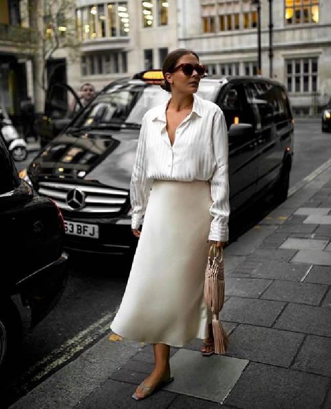 un look printanier avec un chemisier rayé, une jupe midi fluide neutre, des chaussons neutres et un sac à glands blush.