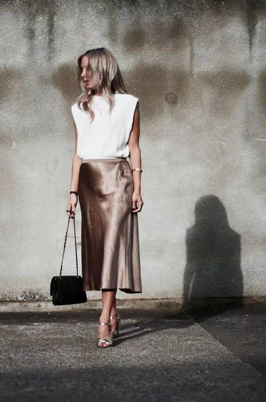 un look estival avec un top oversize blanc, une jupe midi chartreuse, des chaussures argentées et un sac noir
