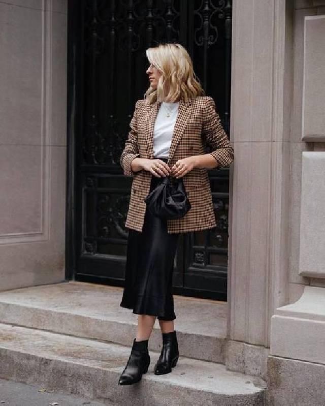 une tenue de travail avec un tee-shirt blanc, un blazer écossais surdimensionné, un pantalon midi noir et des bottines noires.