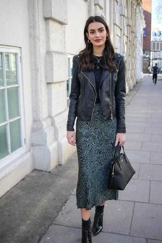 un look sombre avec un tee-shirt noir, une jupe fourreau verte à imprimé animal, des bottines noires, une veste en cuir noire et un sac