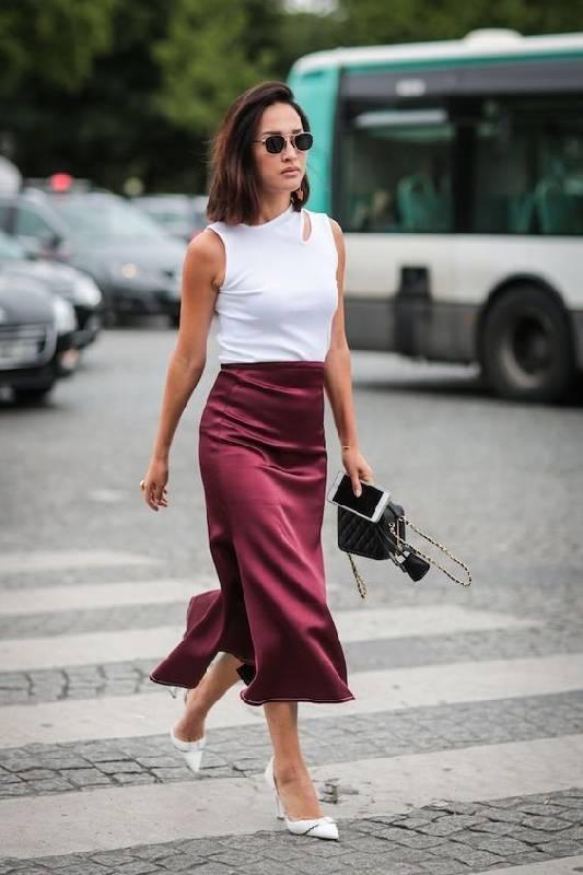 un look printemps-été avec un top sans manches à découpes, une jupe midi bordeaux, des chaussures blanches et un sac noir.