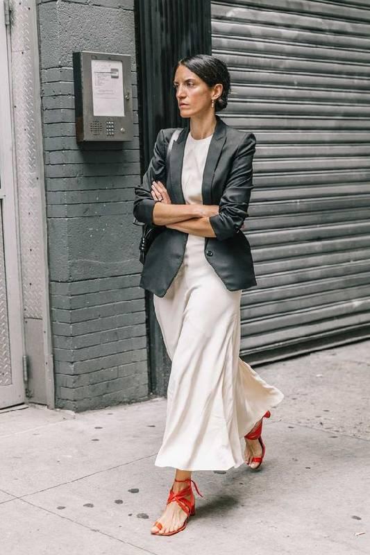 un tee-shirt blanc, une jupe fluide neutre, des chaussures à lanières rouges et un blazer noir pour aller travailler