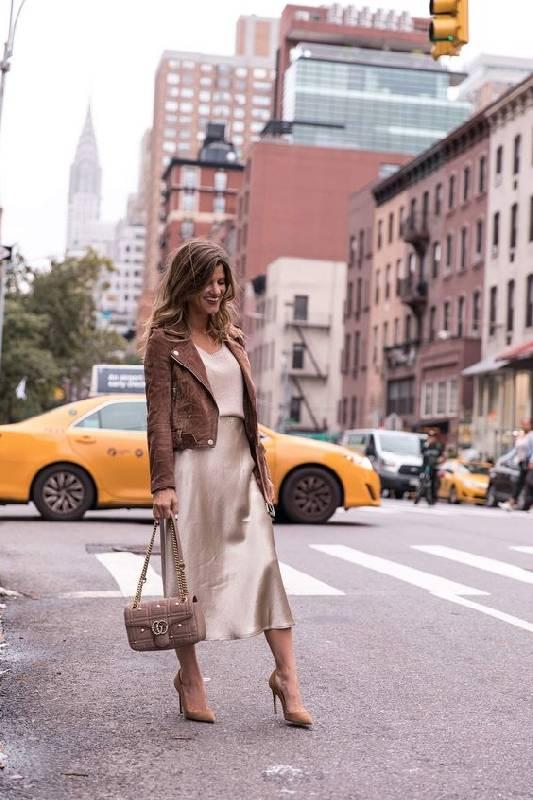 un look aux couleurs sourdes avec un top, un slip midi, des chaussures havane, une veste en daim marron et un sac marron