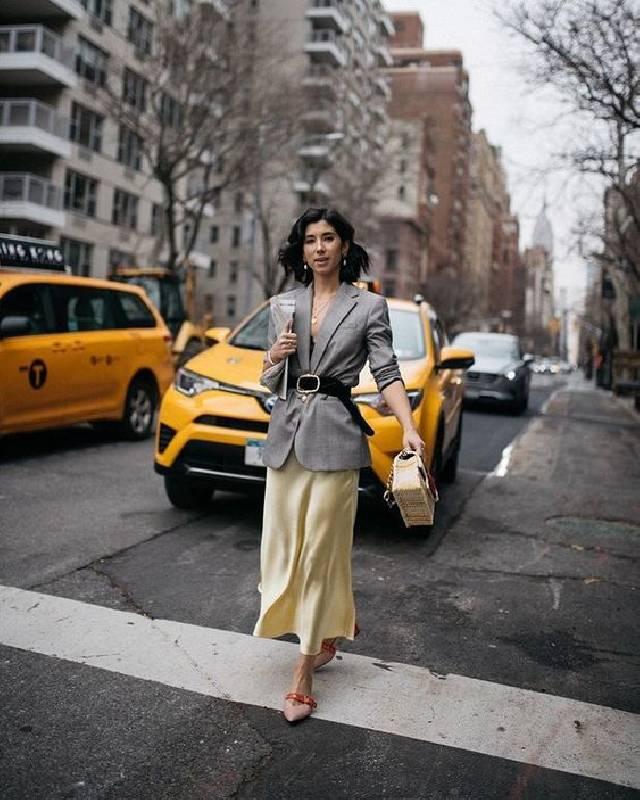 un look de travail accrocheur avec un haut noir, un blazer oversize, une jupe jaune et des chaussures audacieuses.