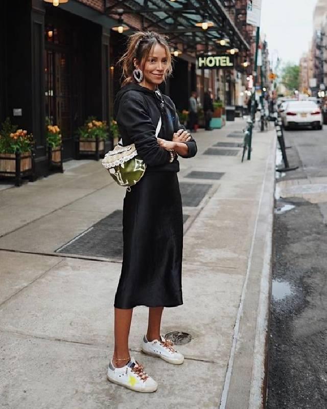 un look accrocheur avec un sweat à capuche noir, une jupe midi fluide, des baskets colorées et un sac brillant